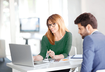 A young couple looking at a computer reviewing retirement fund options.