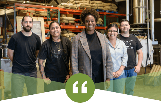 Kenitra Dominguez standing in a warehouse with her co-workers