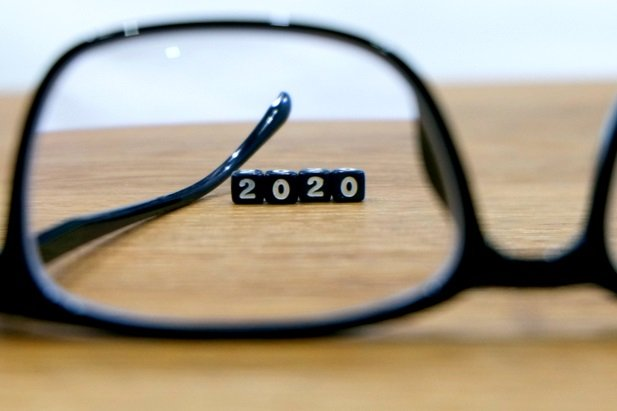 black eyeglasses on table with letters spelling 2020 visible behind them