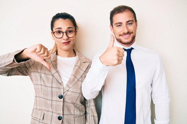 business woman with thumb down, business man beside her with thumb up